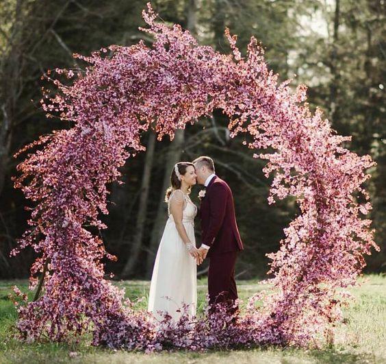 a gorgeous blooming wreath wedding arch features two current trends simultaneously
