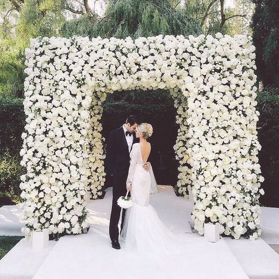 a modern and luxurious wedding chuppah fully covered with white roses is a stunning statement