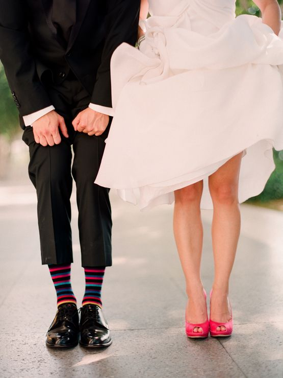 the bride showing off her bright heels and the groom showing off his funny colorful socks