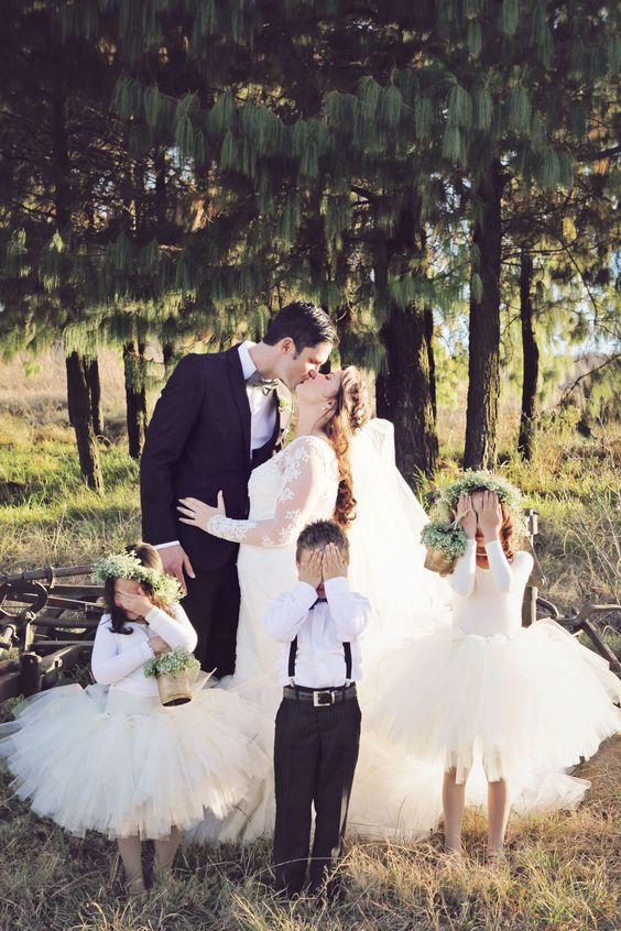 the couple kissing and flower girls and a ring bearer hiding from that to keep it more private