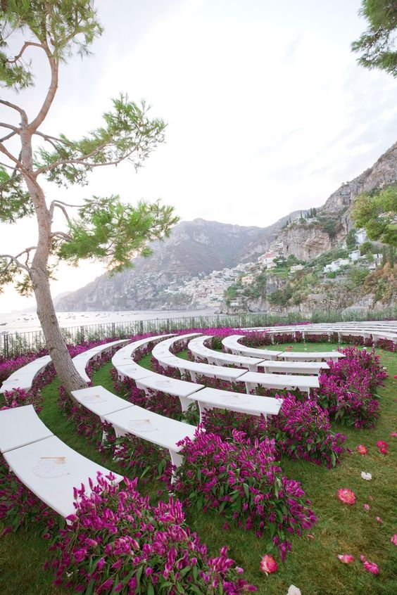 a wedding ceremony space done with purple blooms even under the benches is a gorgeous modern idea