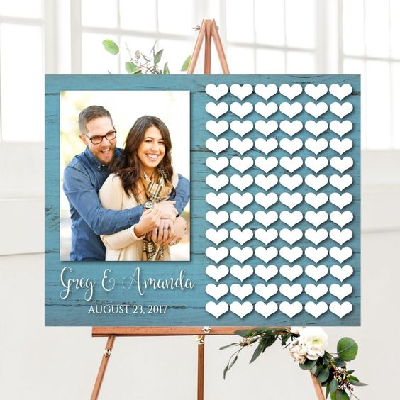 a stylish wedding guest book of a blue wooden sign, a large couple photo and lots of wooden hearts attached
