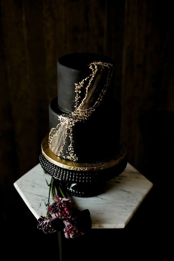 an edgy black wedding cake with gold foil and marble detailing for a modern wedding