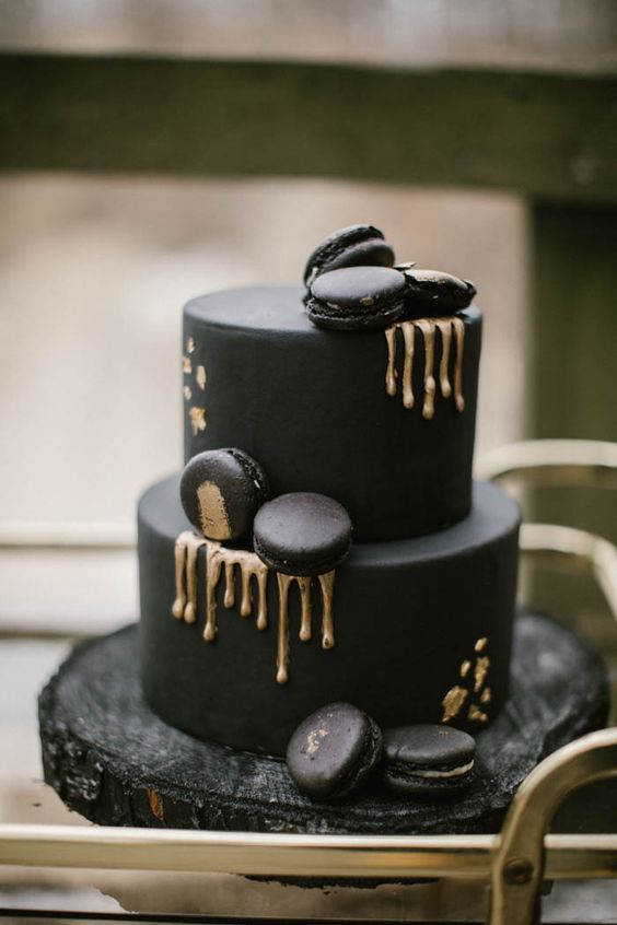 a matte black wedding cake with black macarons and gold drips looks very eye-catchy