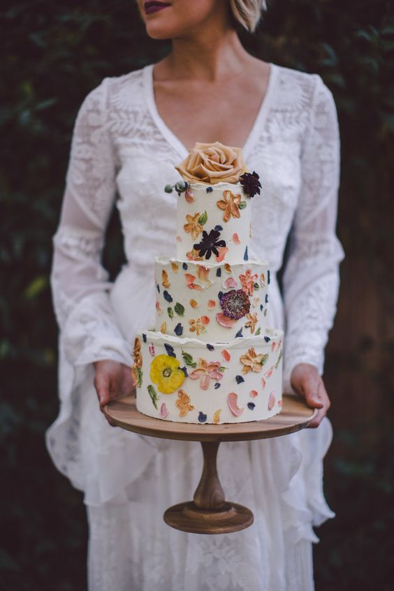 a boho chic wedding cake with painted and pressed blooms plus a single bloom on top