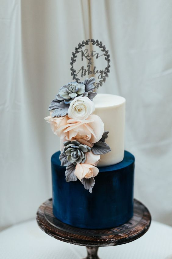 a color block wedding cake with a white and navy tier, with fresh and sugar blooms plus a topper