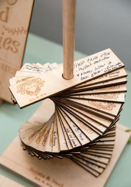 a copper stand with lots of wooden planks with burnt hearts and wishes from your guests