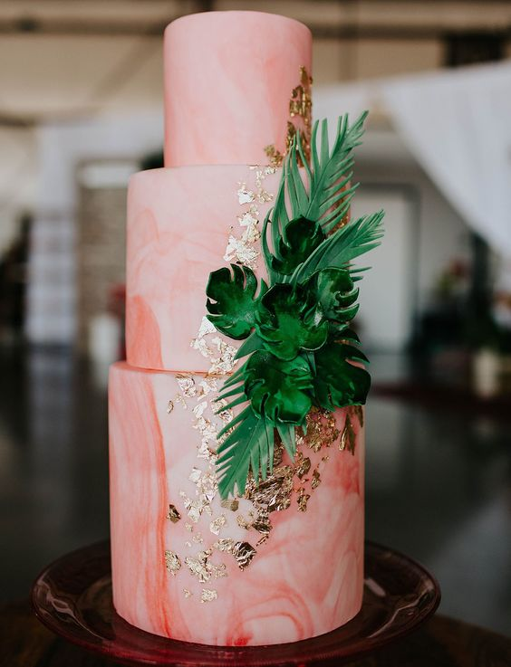a watercolor coral wedding cake decorated with gold leaf and sugar tropical leaves as an accent