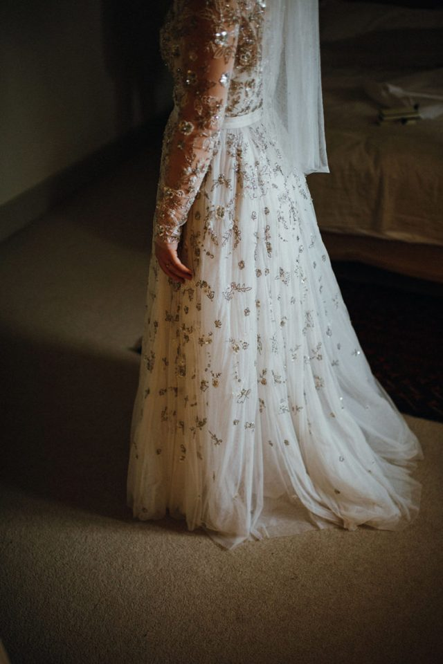 The bride was wearing a fully embellished wedding dress with an illusion neckline, long sleeves
