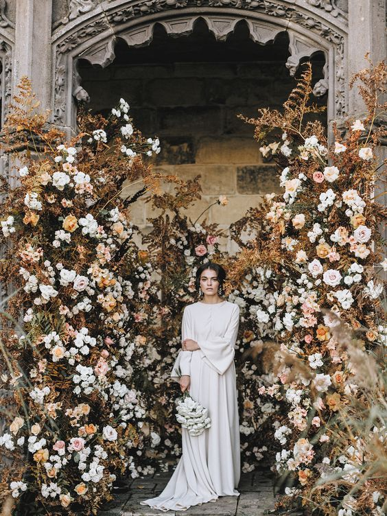 a jaw-dropping wedding installation with dried herbs and white and blush blooms for a beautiful fall wedding