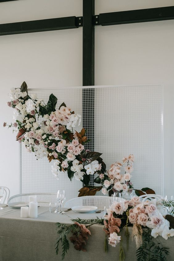 a white mesh sweetheart table backdrop with dark and green foliage and lush blush and white blooms