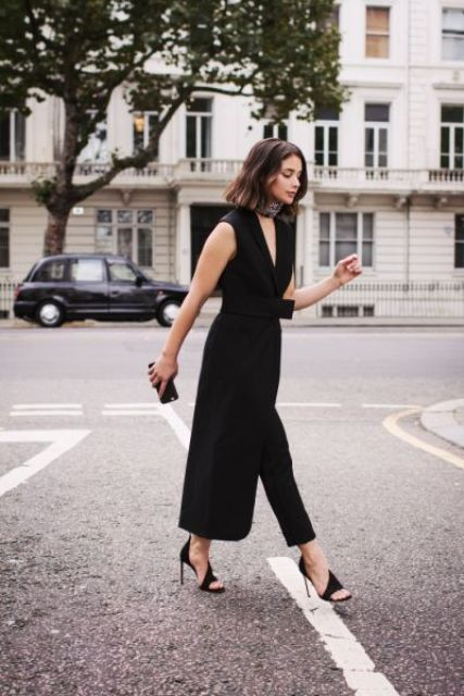 black cropped pants, a black sleeveless waistcoat with a sash, catchy black heels and a tiny clutch