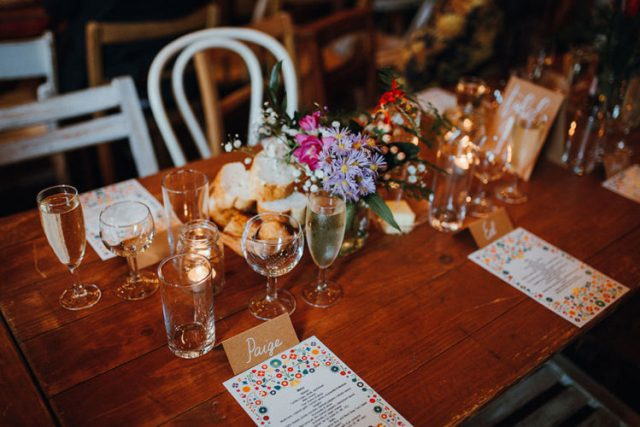 The wedding reception tables were done with bright blooms and bright menus