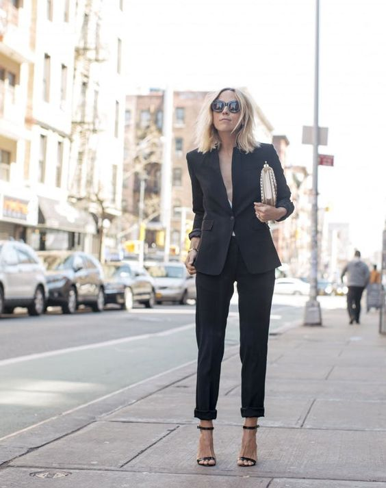a black pantsuit with no top under, a metallic bag and black heels for a sexy look
