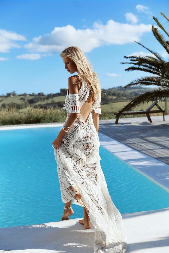 a halter neckline boho wedding dress with tassels that cover the whole bodice and cutout back