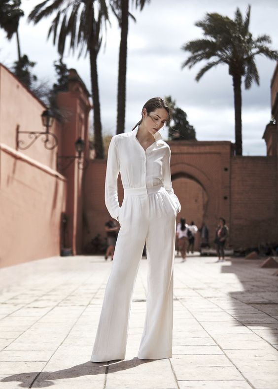 a white jumpsuit with wideleg pants and long sleeves requires only heels, statement earrings and a little clutch