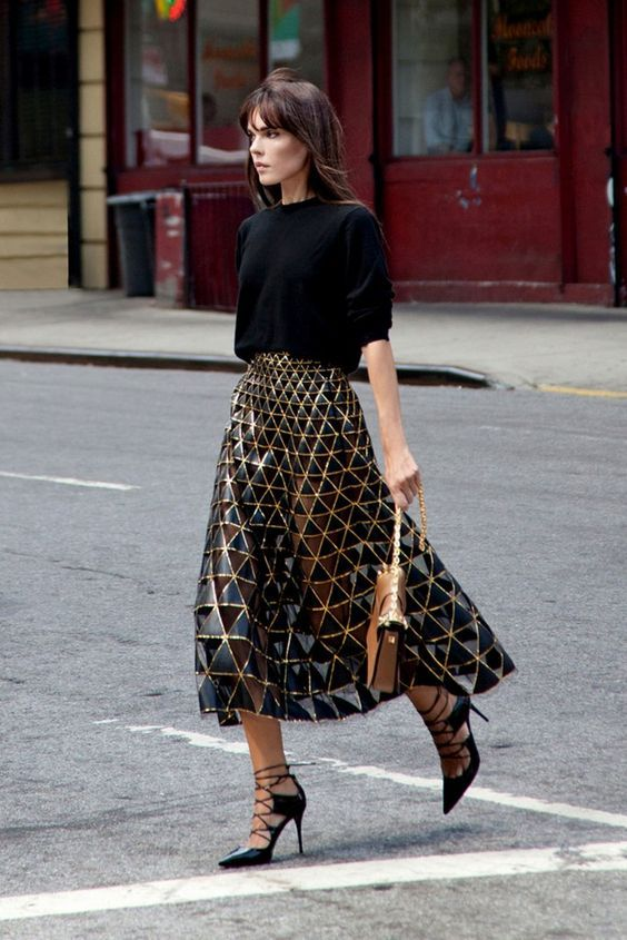 a black oversized sweater, a blakc and gold geometric midi skirt, black lace up shoes and a camel bag