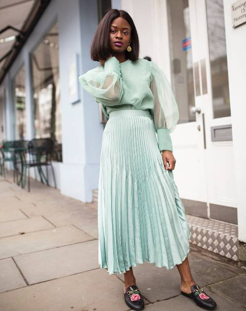a mint green pleated midi skirt styled with a matching blouse with puff sleeves and floral slip mules