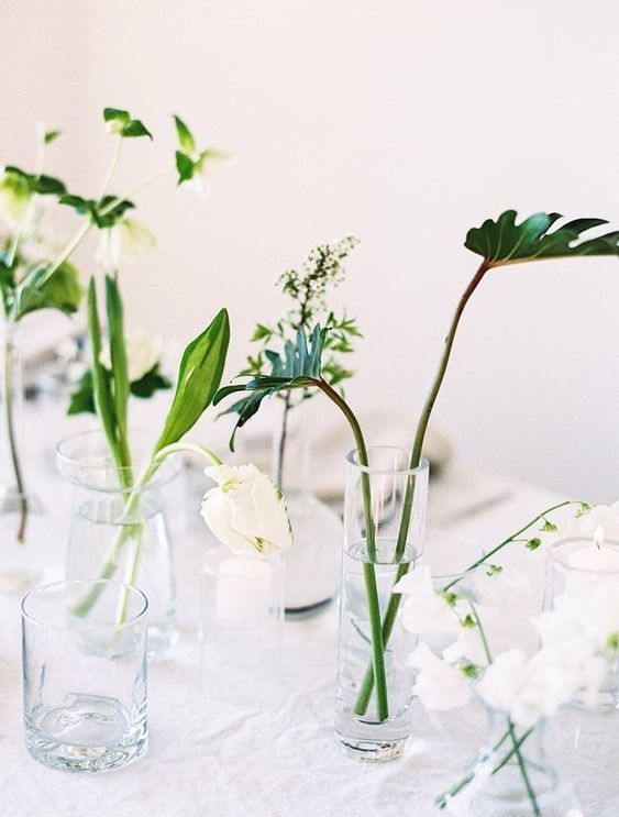 an arrangement of clear glasses with various leaves and some white blooms is a simple minimalist idea
