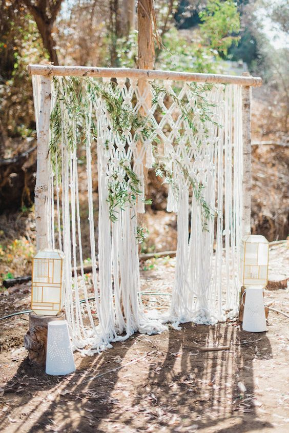 a cool macrame wedding backdrop with greenery interwoven and catchy geometric candle lanterns