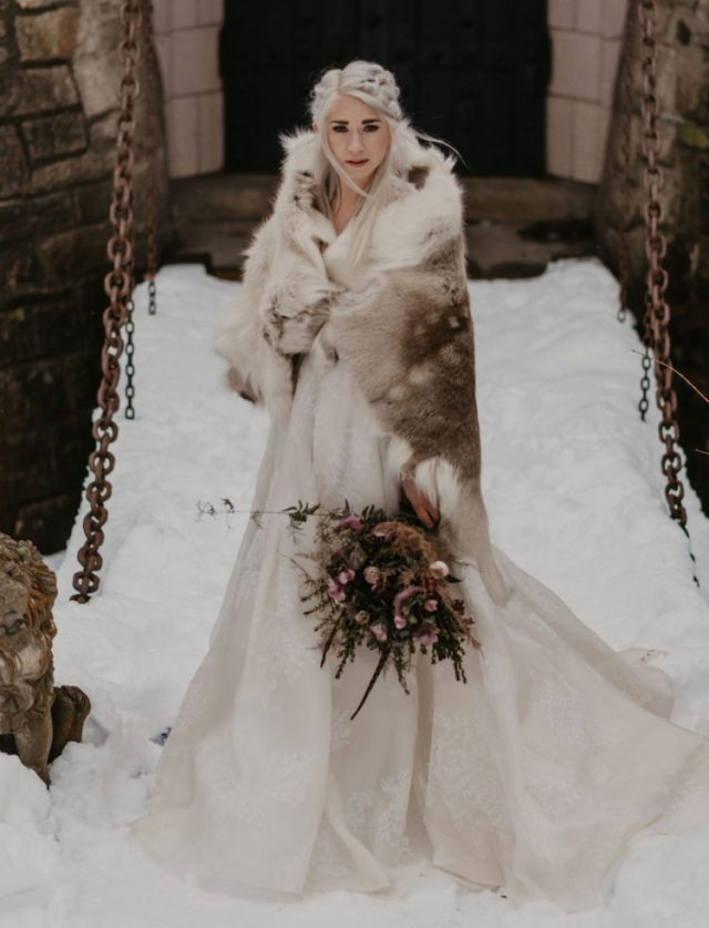 Daenerys-styled bride in a lace wedding ballgown, with a braided hairstyle and a fur coverup