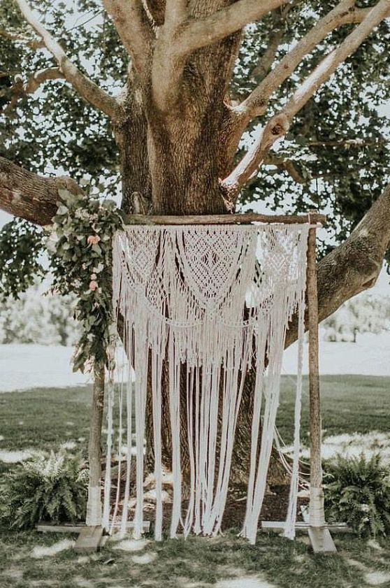 a relaxed summer wedding backdrop of macrame and some greenery and pink blooms hanging on one side
