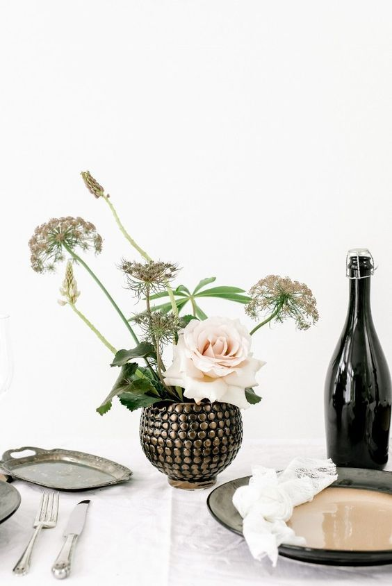 a very catchy embellished round vase with some dried blooms and a single blush roses has a big impact