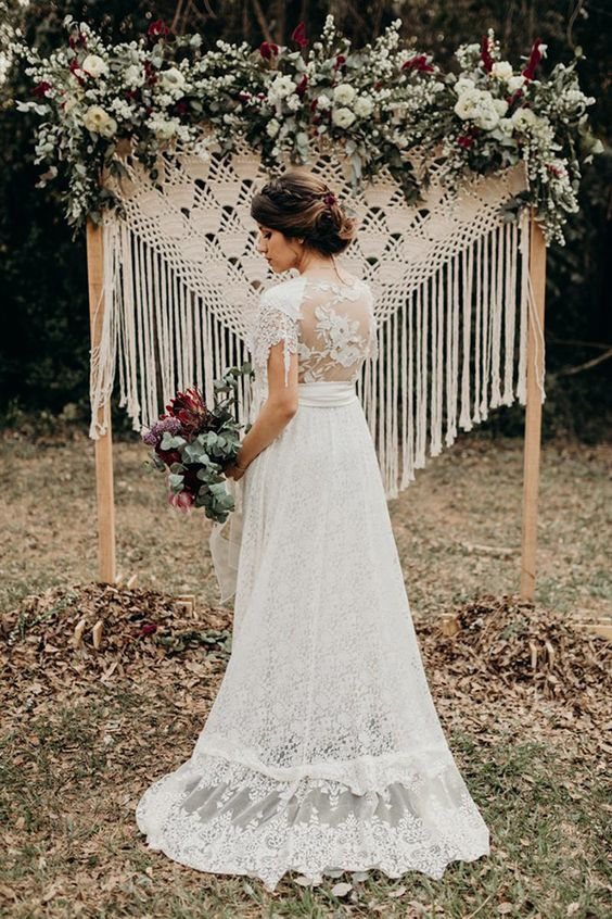 a macrame wedding backdrop with long fringe, lush greenery and lots of white blooms for a summer wedding