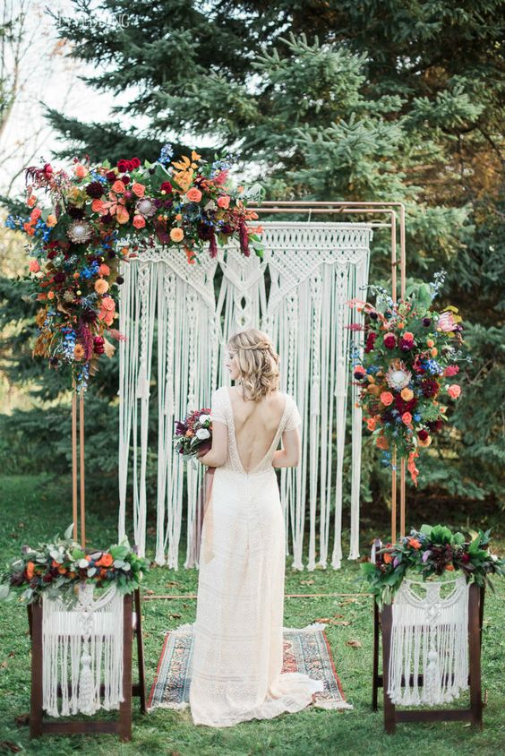 a macrame wedding backdrop with bright orange, burgunyd, peachy pink and blue flowers plus greenery