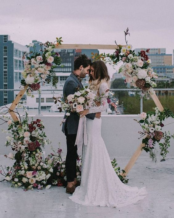 a hexagon wedding arch with super lush florals in pink, blush, burgundy and some leaves and branches