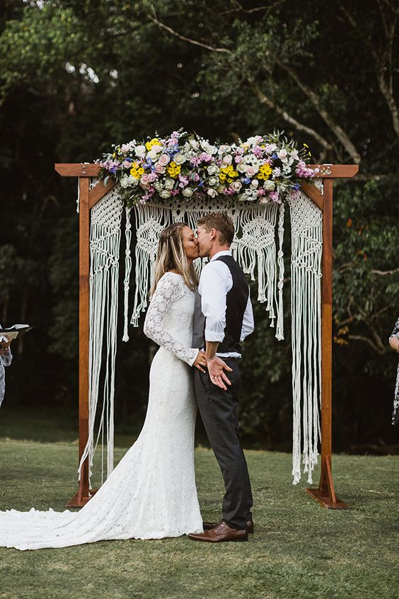 a bright boho summer wedding arch with macrame and lush blooms in pink, lilac and yellow on top