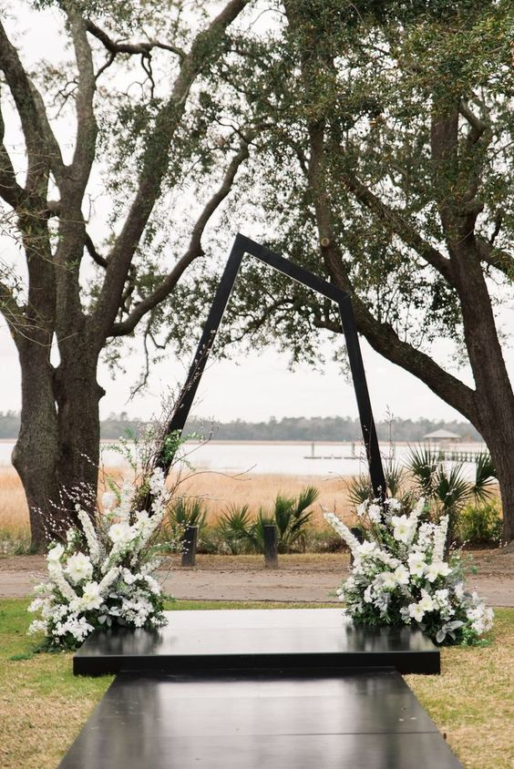 a dark stained asymmetrical geometric wedding arch with lush white blooms and greenery at its base