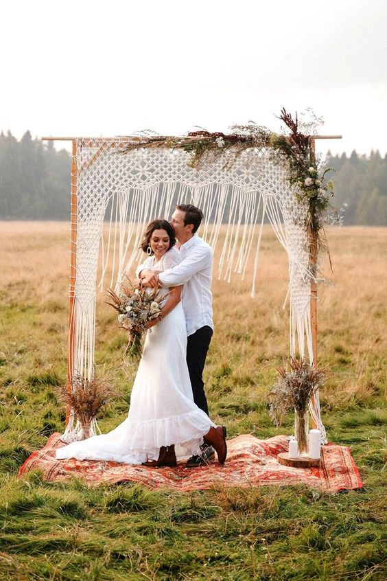 a fall boho wedding arch with macrame, some dried leaves and herbs plus white blooms, candles and dried herb arrangements