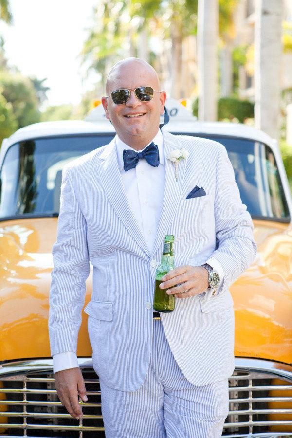 a blue thin stripe suit, a white shirt, a navy polka dot bow tie for a nautical or beach wedding