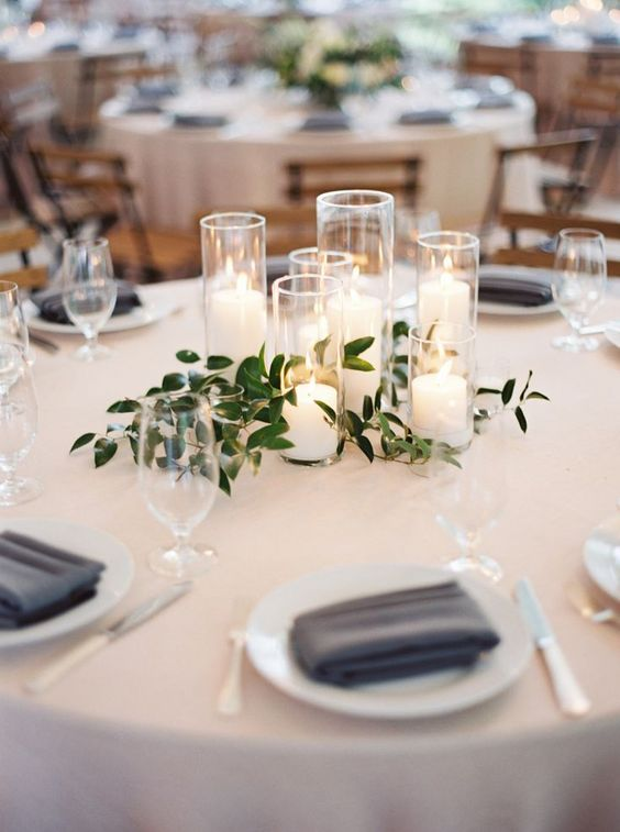 a group of candles with greenery is a chic minimalist wedding centerpiece that creates a cozy ambience at the table