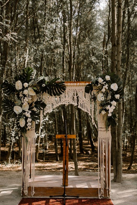 a tropical wedding arch with macrame, lush white tropical blooms and tropical leaves