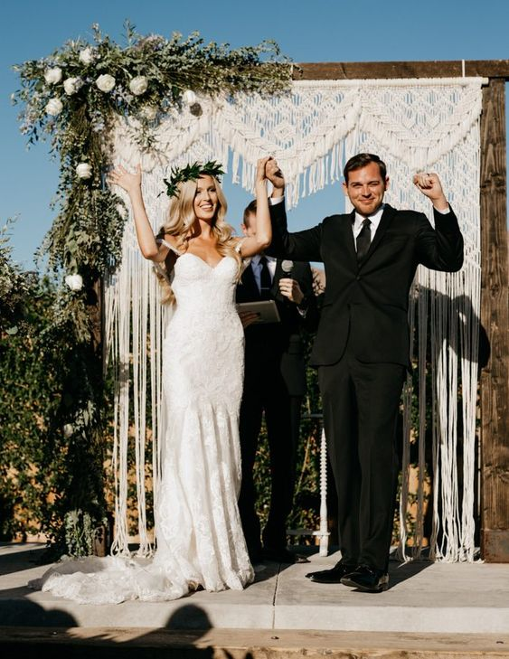 a wedding arch decorated with macrame and fringe, with lush greenery and white blooms on one corner