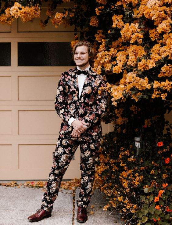 a moody floral suit, a white shirt, a black bow tie and burundy shoes is a bold option for a fall wedding