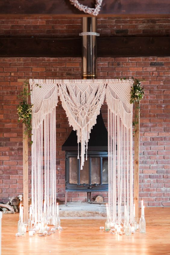 a wedding arch with macrame decor, some foliage and candles in bottles around to highlight it