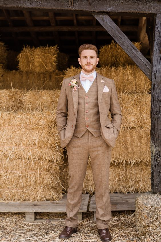 a striped brown three-piece tweed suit, a white shirt, a blush bow tie and brown shoes for a rustic wedding