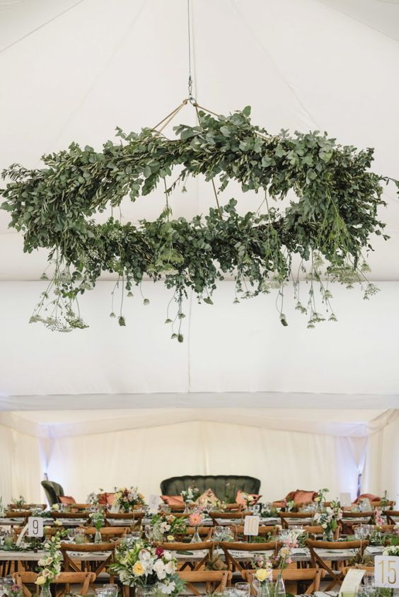 a statement greenery chandelier with hanging elements takes over the whole reception space