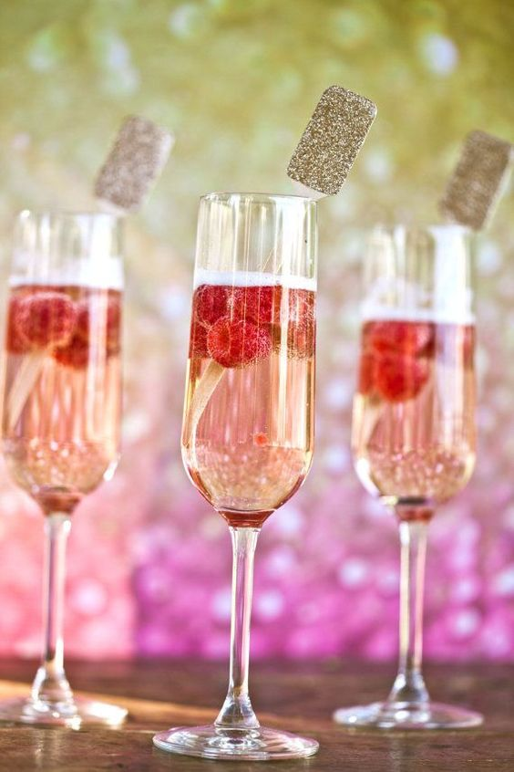 signature drinks with raspberies and wooden drink stirrers with gold glitter tops are amazing