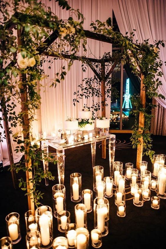 a wedding arch repurposed into a decoration to highlight the wedding cake table