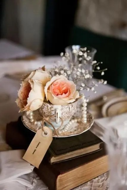 a stack of vintage books, a vintage teacup with fresh blooms, pearls, baby's breath and a tag for a vintage wedding