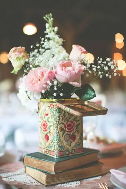 a stack of books with a tin can and a pink floral arrangement will fit a boho or a rustic wedding