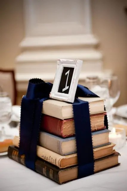 a stack of vintage books with navy ribbon to match the wedding color scheme and a table number on top