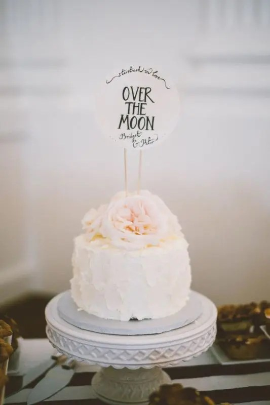 Picture Of a textural white buttercream wedding cake topped with blush peonies on top and a