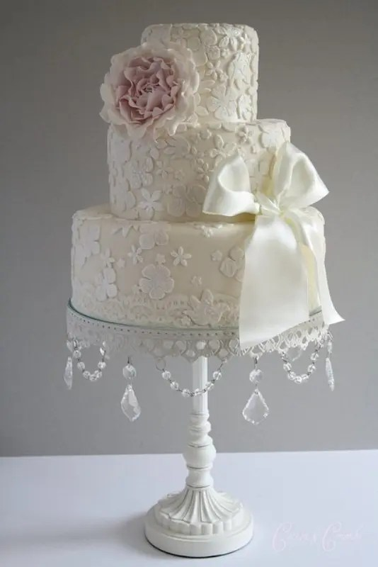 Picture Of a neutral floral lace wedding cake with a neutral bow and a blush sugar bloom on top