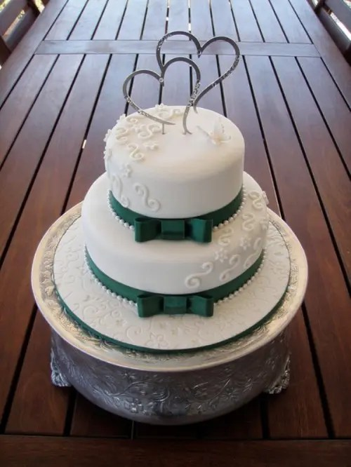 an elegant white wedding cake with patterns and emerald ribbons and bows