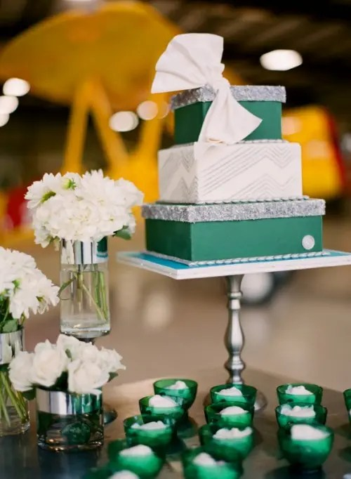 a white and emerald wedding cake with geometric patterns and a large bow